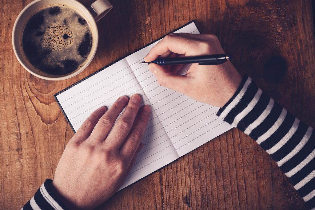 Woman drinking coffee and making a diary note, top view of female hands writing in notebook, retro toned image with selective focus.